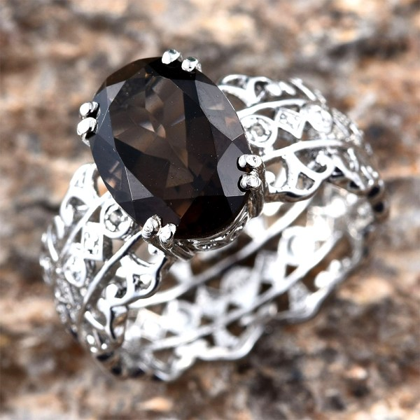 Smoky quartz ring against rocky background.