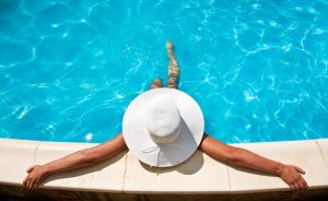 A woman in a floppy hat lounging in the pool.