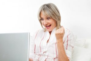 Senior woman winning an online auction.