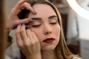 Woman having black eyeliner applied.
