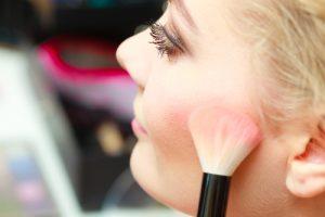 Woman applying blush to her cheek.