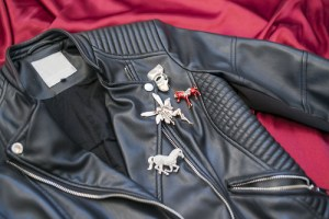 Leather jacket decorated with pins and brooches.
