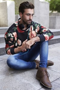Man wearing black floral print shirt with denim pants.