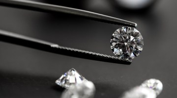 Closeup of diamond held by tweezers