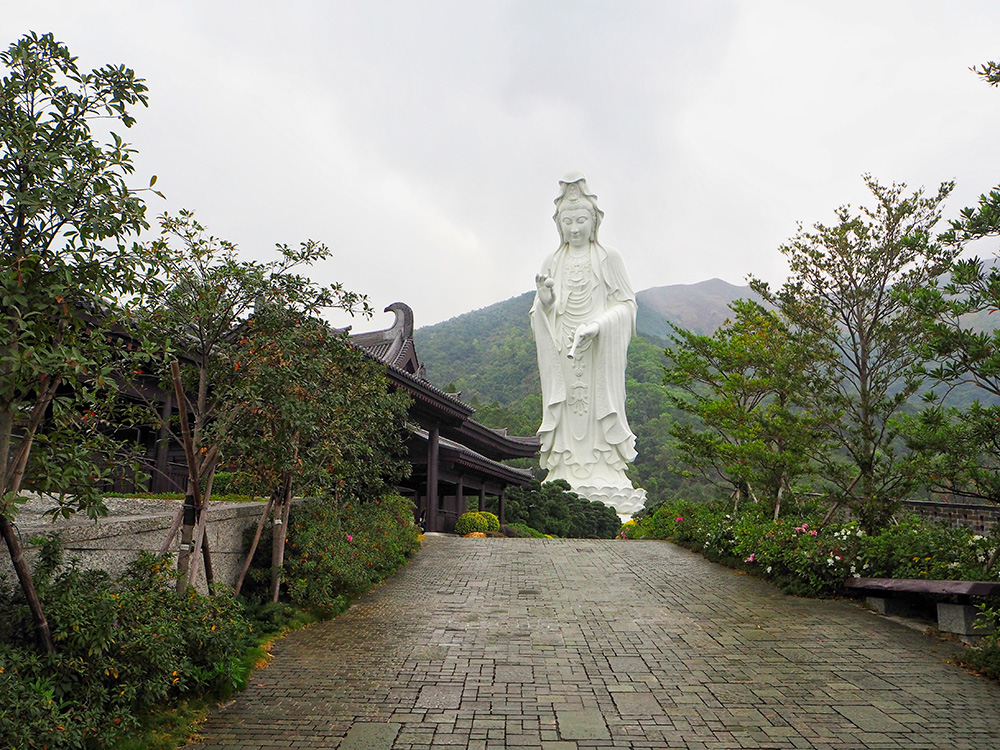 Statue of Guan Yin in Hong Kong against green forest.
