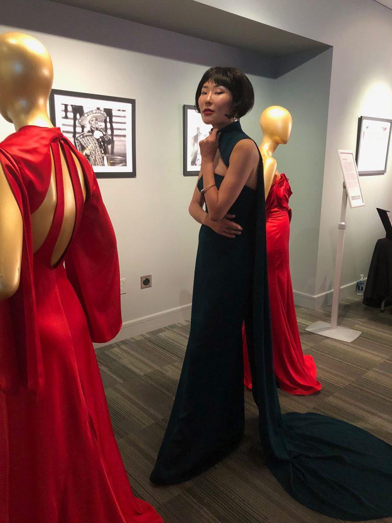 Asian model in a green dress showcasing Shop LC jewelry.