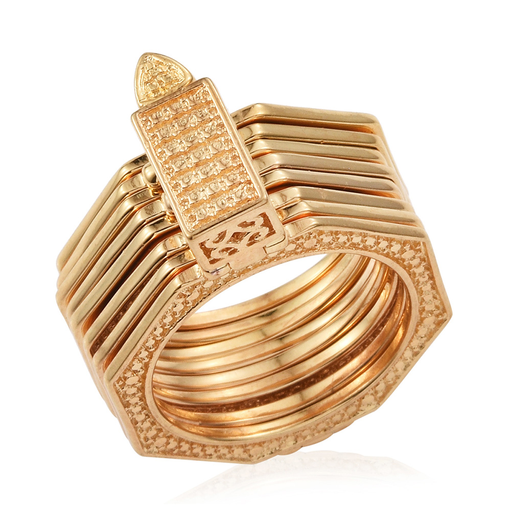 Set of gold bracelets against white background.