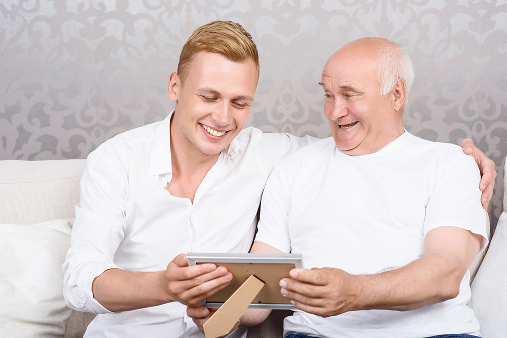 Grandpa and grandson reminiscing over a photo