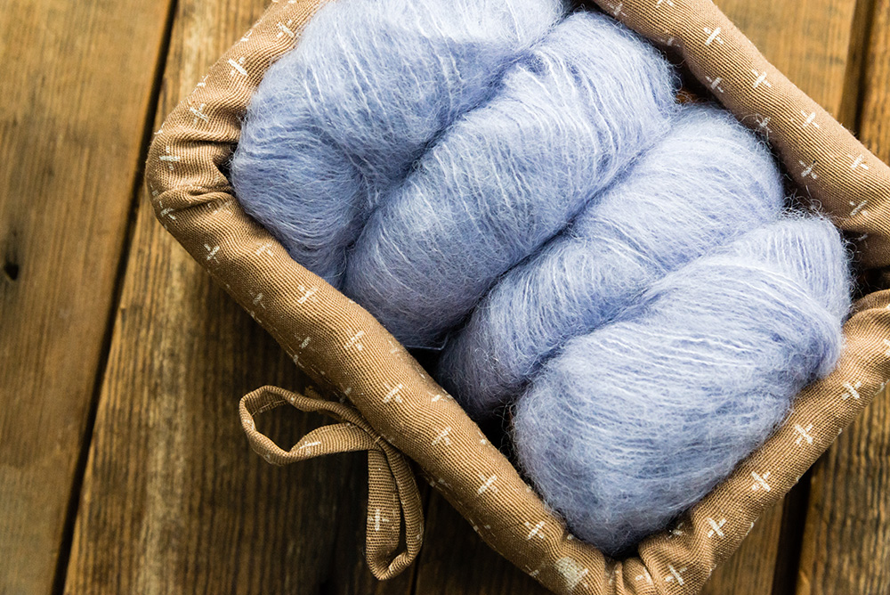 Light blue yarn in basket on wooden floor