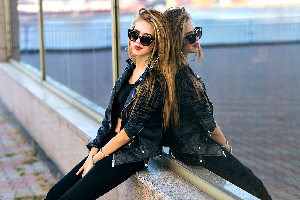 Woman wearing black leather jacket leaning against window with sunglasses on