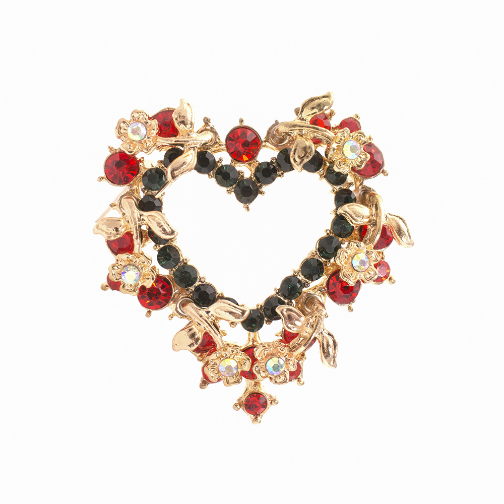 Closeup of flower heart brooch against white background