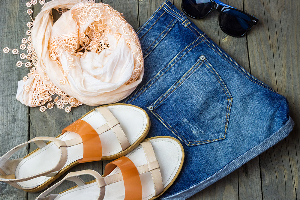 Flat lay of woman's outfit with denim and brown