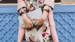 Closeup of floral dress and blush pink coat holding a teal clutch