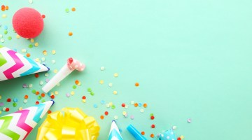 Confetti and party hat against teal background