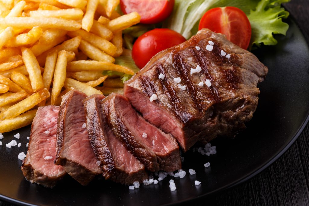 New York strip steak cooked medium rare with fries.