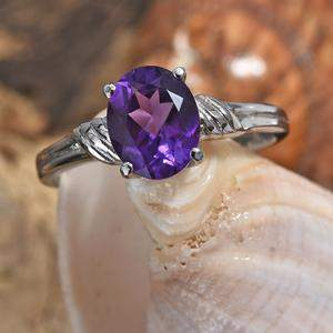 Amethyst ring displayed on shell.