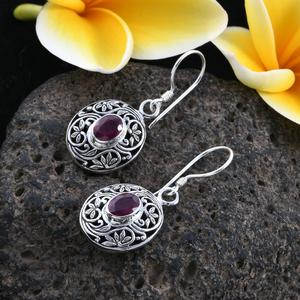 Ruby earrings in sterling silver against gray lava stone.