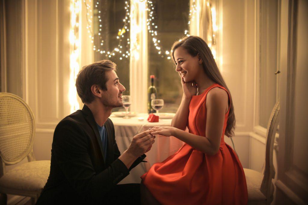 Man proposing to woman during candlelit dinner.
