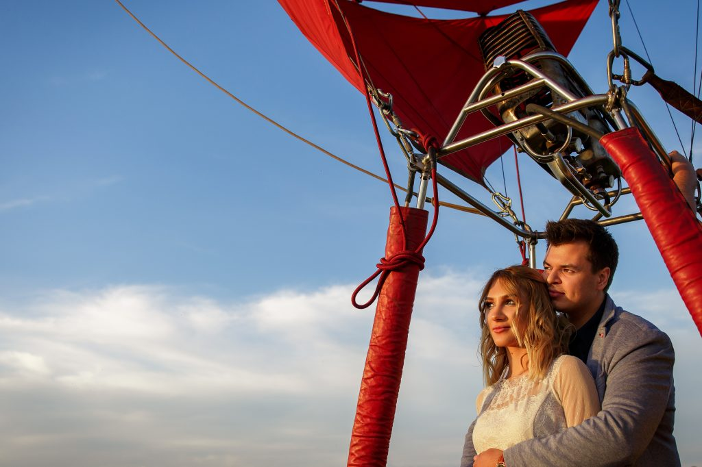 Couple sharing romantic hot air balloon flight.