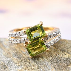 Peridot bypass ring with zircon accents resting on stone for display.