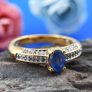 Burmese blue sapphire and yellow gold ring on wood display.