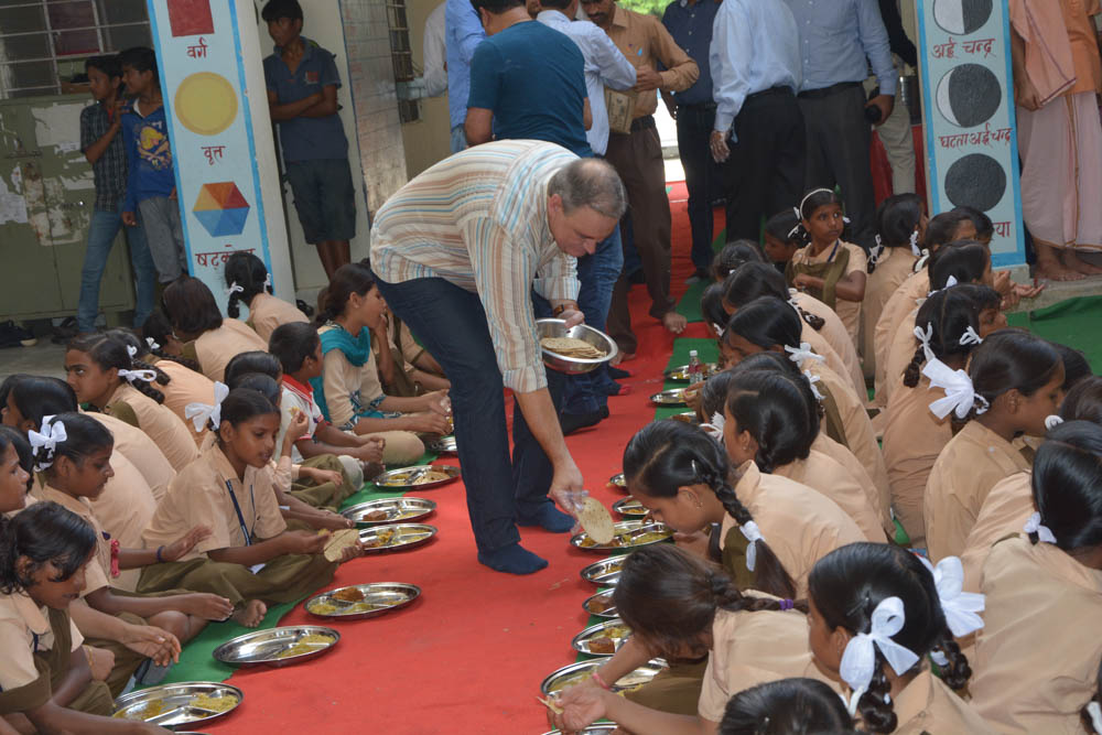 Shop LC President Kevin Lyons serving meals to school children.