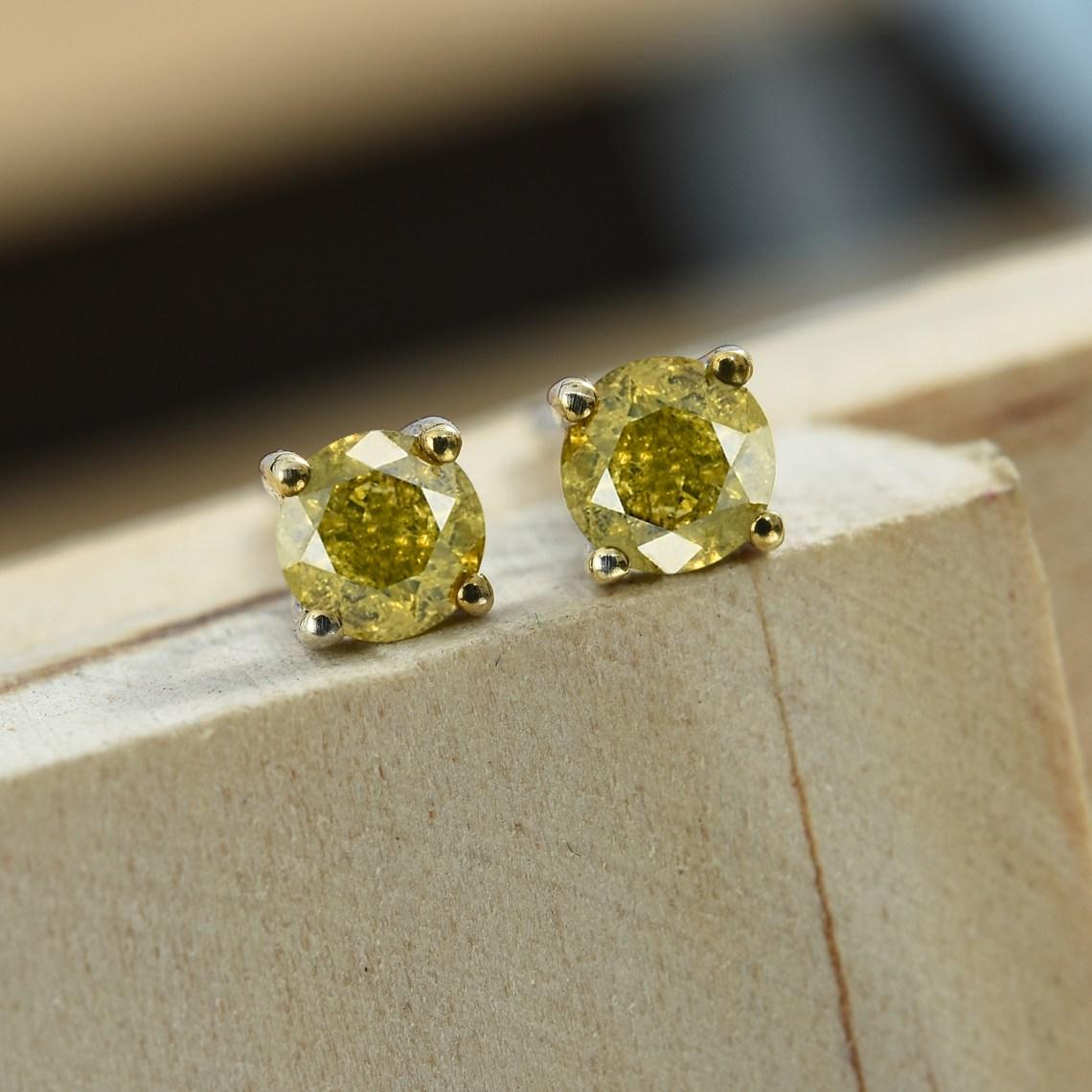 Yellow diamond stud earrings displayed on wooden plinth.