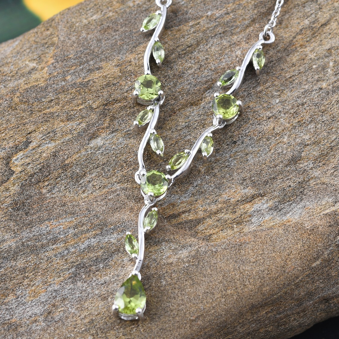 Peridot necklace carefully draped over stone.