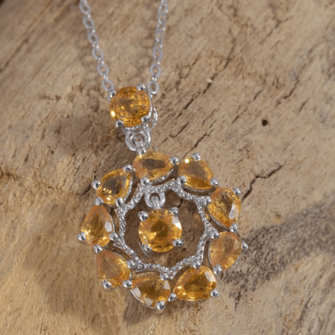 Yellow sapphire pendant necklace draped over wood.