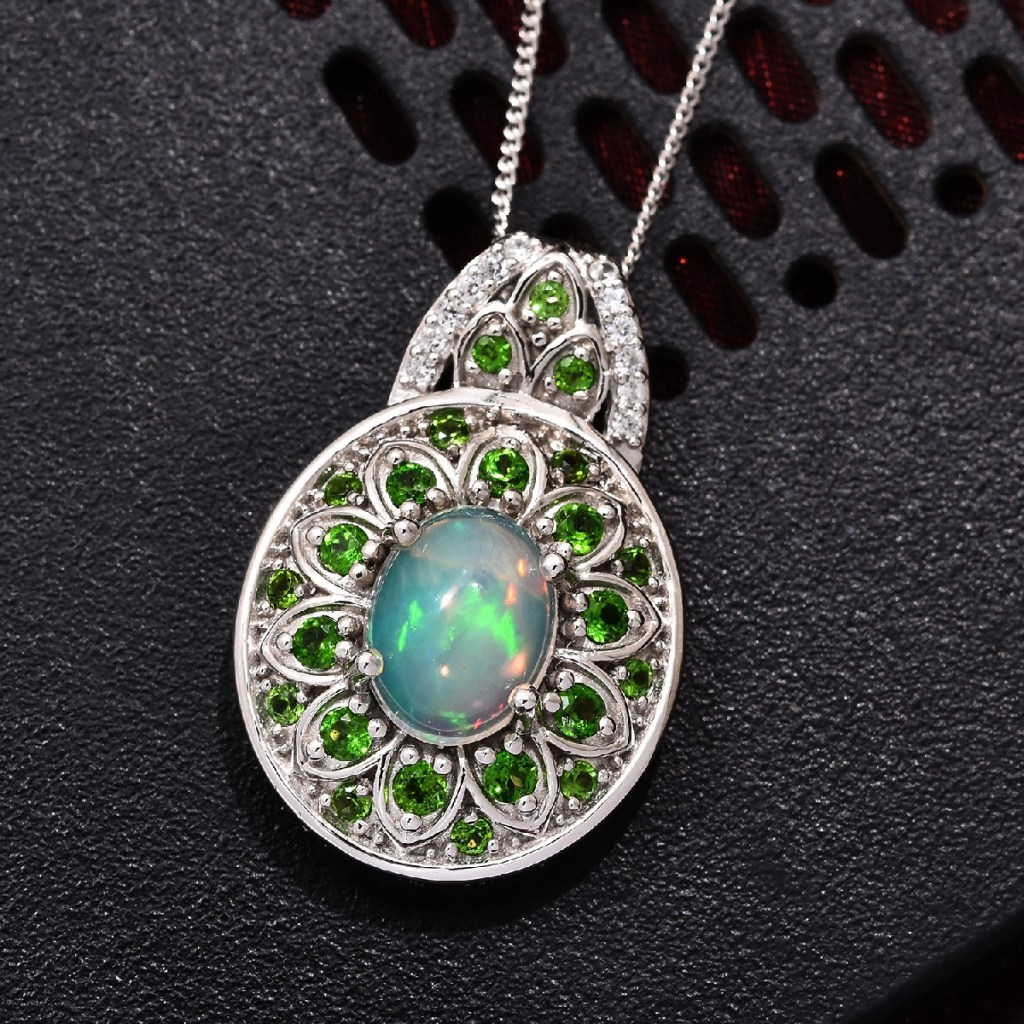 Welo opal pendant in silver against black background.