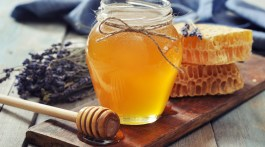 Honey in jar with honey dipper on vintage wooden background