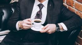 A man in a suit with a cup of coffee sits on a black leather sofa.
