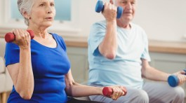 Senior couple lifting dumbbells while sitting on exercise ball at home.