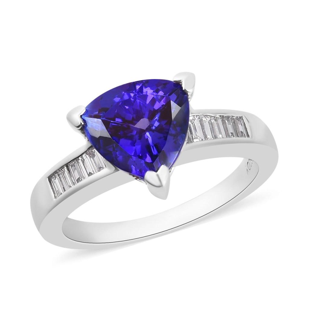 Triangle-shaped blue gemstone in platinum setting.