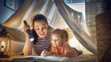 Mom and kid reading inside pillow fort.