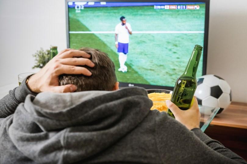 hombre sufriendo al ver a su equipo por tv