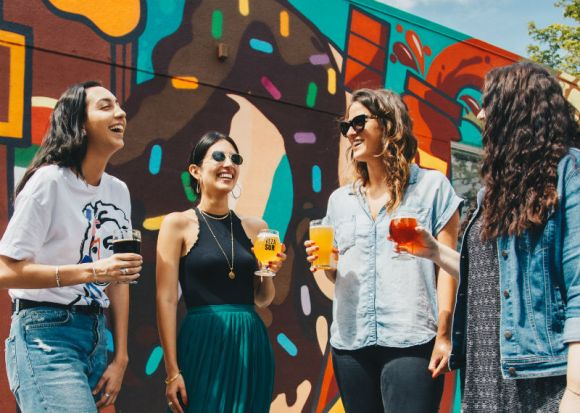 Chicas bebiendo cerveza al sol.
