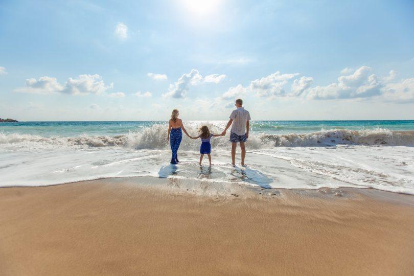 Familia en una playa entrando en el mar.