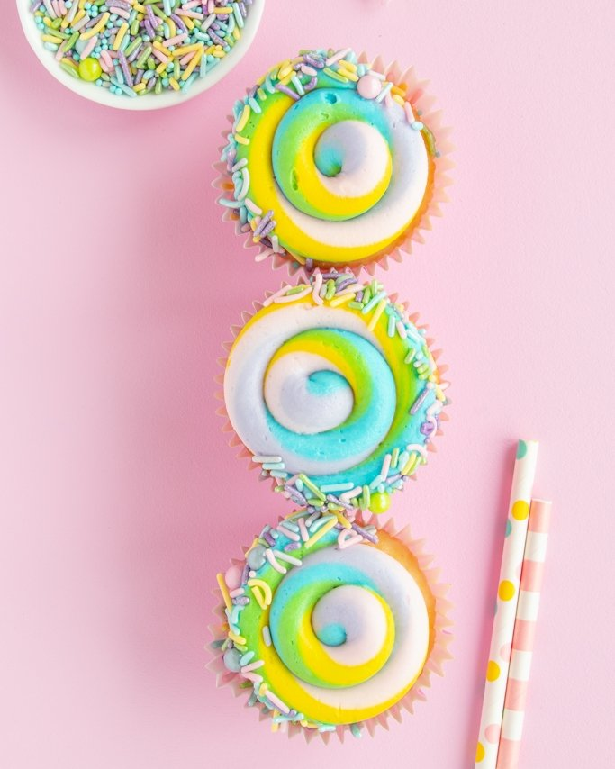 Pastel swirl Easter cupcakes with pastel sprinkles trim on light pink background