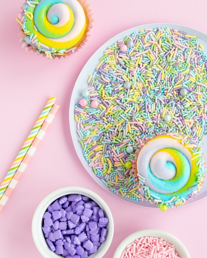 Easter Party Ideas - Pastel sprinkles on plate and light pink background with candy sprinkles around border on photo.
