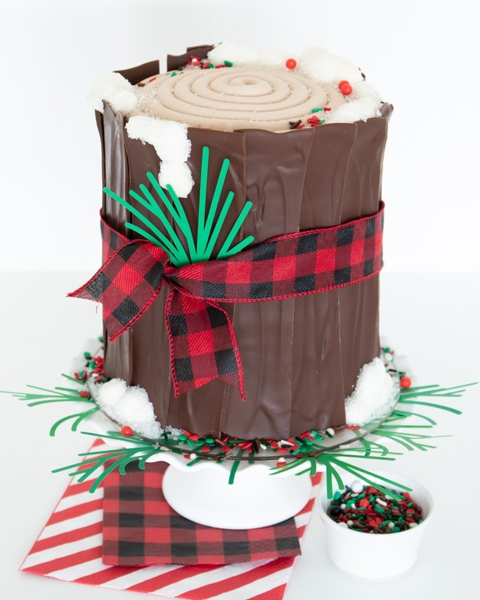 finished Christmas log cake topped with lumberjack sprinkles and tied with a buffalo plaid ribbon