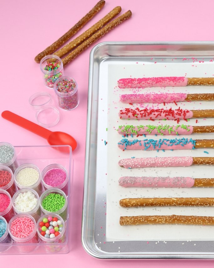 Merry & Bright Sprinkled Chocolate Covered Christmas Pretzels - This Christmas treat is so easy and fun. Dip with the kids or by yourself for your next party. Change up the colors using different sprinkle mixes or color coating chocolate. In just a few minutes, you'll have pretty party sweets for your sweets table!