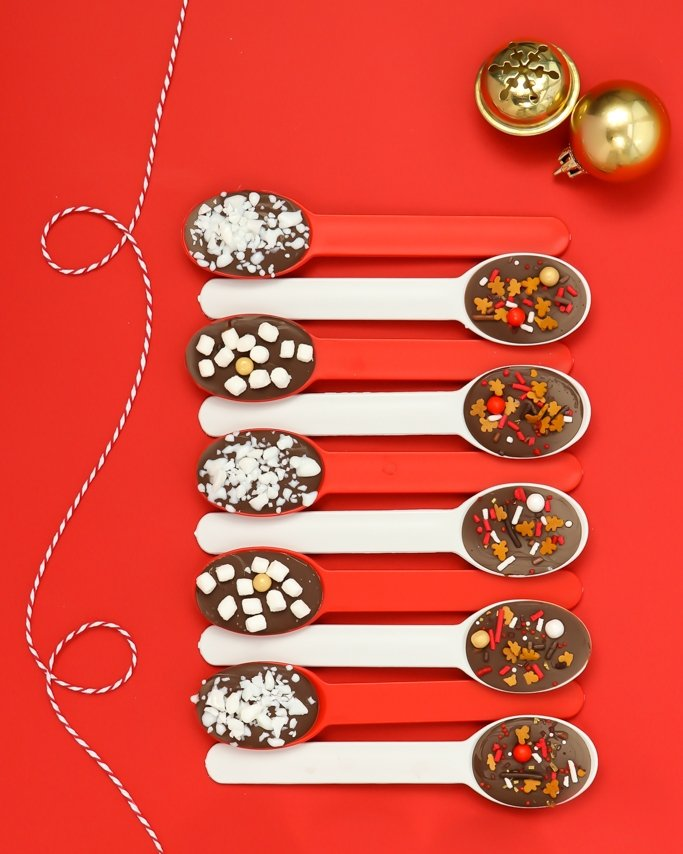 Cocoa & Cookies Christmas Party Ideas, Chocolate Cocoa Spoons on red back ground with red and white plastic ice cream spoons