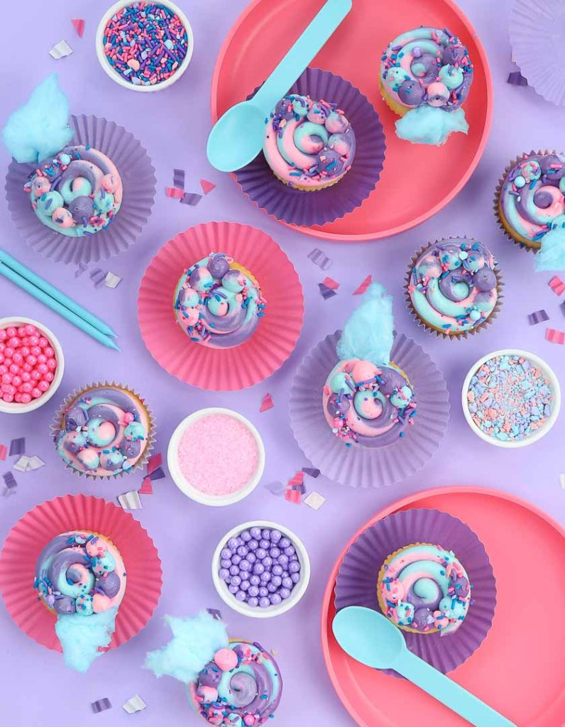 Cotton candy cupcakes laid out on purple background for party