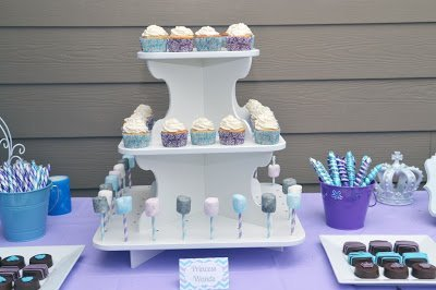 Cupcake stand with cupcakes and cake pops on purple table cover.