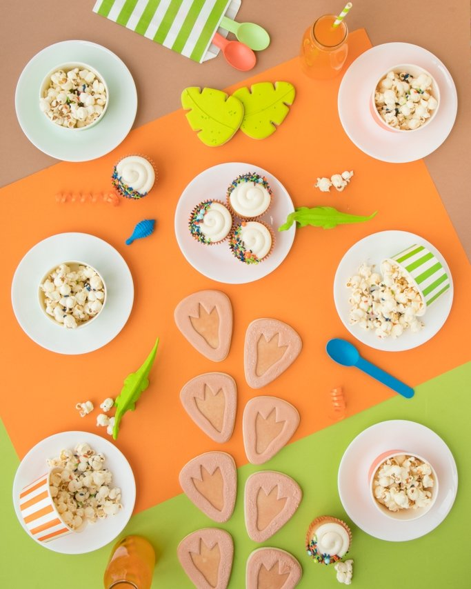 Dinosaur Party Ideas Tablescape on orange, lime green, and brown background