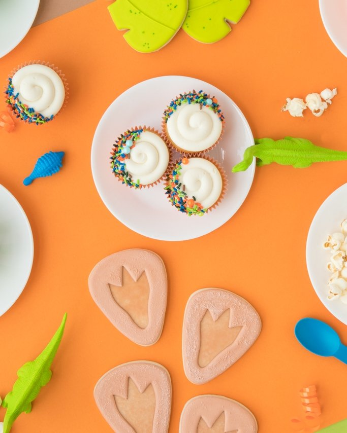 Dinosaur Birthday Party Cupcakes and footprint cookies on white plate and orange background