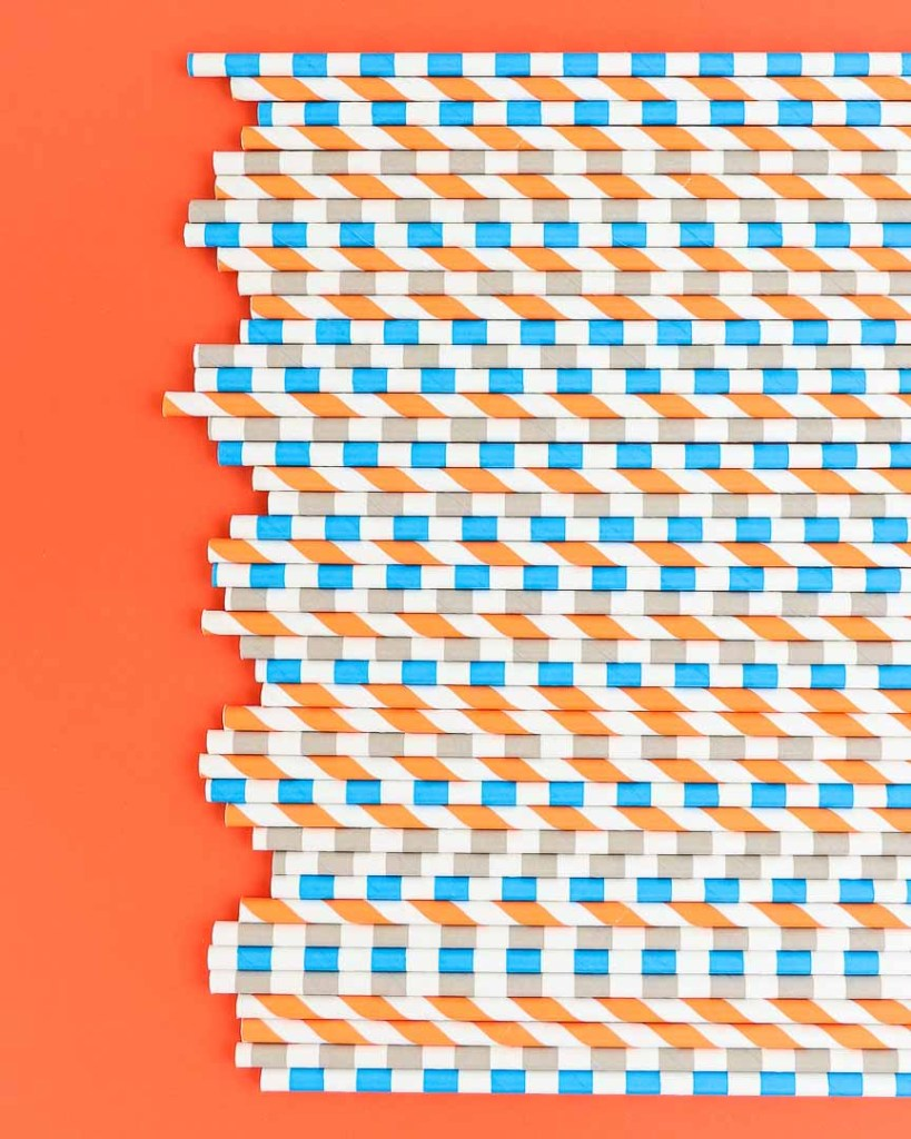 Assortment of orange, blue, gray, and white paper straws