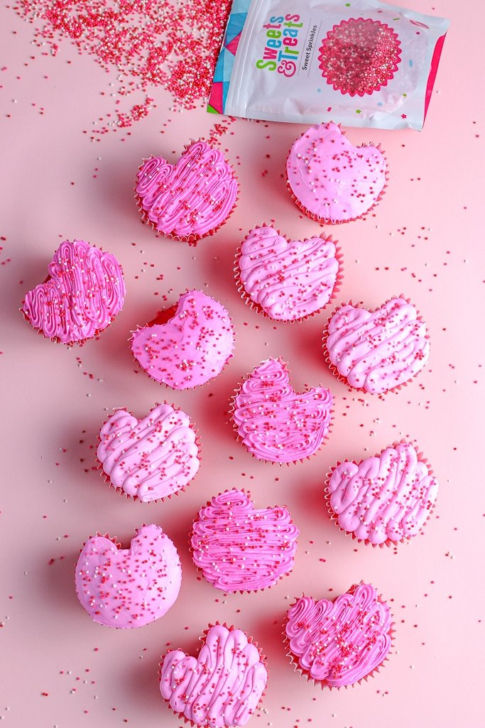completed heart shaped cupcakes with their varying shades of pink icing and sprinkles
