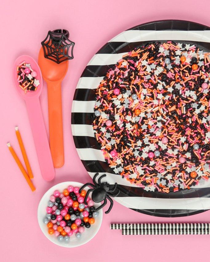 Hocus Pocus Halloween Sprinkle Mix on black striped plate on pink background